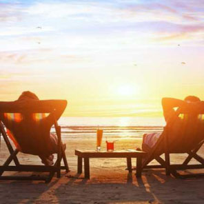 Couple lying back on sun chairs on a beach watching the sun set