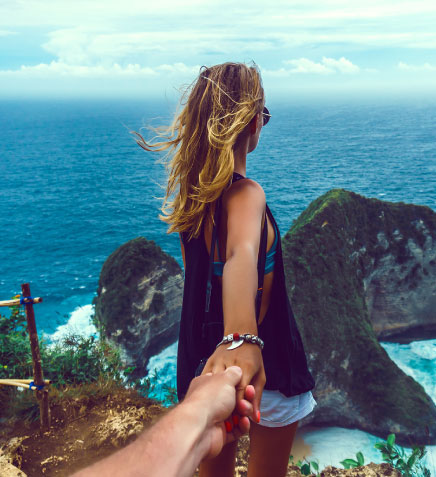 blond woman standing on cliff overlooking the ocean holding a man's hand