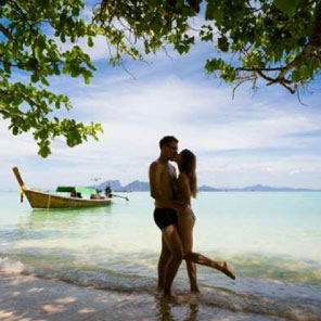 silhouette of man and woman kissing on a beach with boat behind