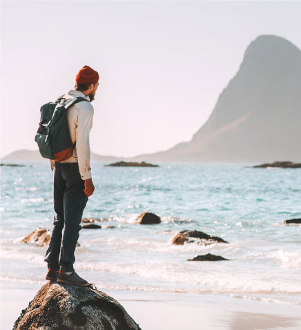 Man in red hat standing on a rock overlooking beach, ocean and mountains