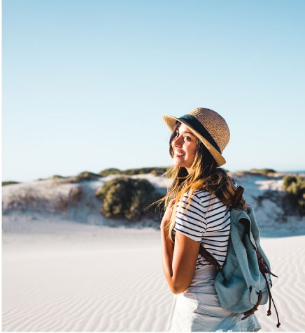 woman in straw hat and stripey t-shirt smiling on a beach