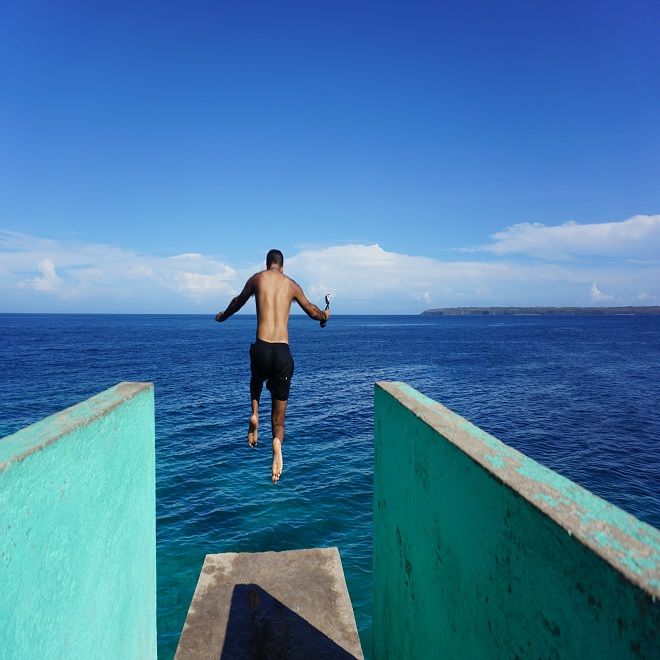 man jumping off board into ocean
